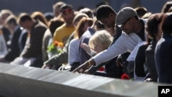 受难者家属2012年9月11日在纽约纪念911 恐怖分子袭击纽约世贸中心11周年之际,观看铭刻在纪念台上受难者的姓名