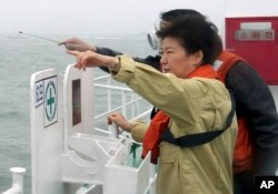 FILE - South Korean President Park Geun-hye looks at the site where the Sewol sank from aboard a Coast Guard ship in waters off the southern coast near Jindo, South Korea, Thursday, April 17, 2014.