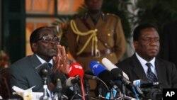 FILE: Zimbabwean President Robert Mugabe, left, and Defense Minister Emmerson Mnangagwa, at State House press conference, Harare, July, 30, 2013.