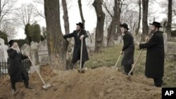 Rabbis take a break from the reburial remains of Holocaust victims found in a mass grave in northern Romania, at the Jewish cemetery in Iasi, Romania, Monday, April 4, 2011