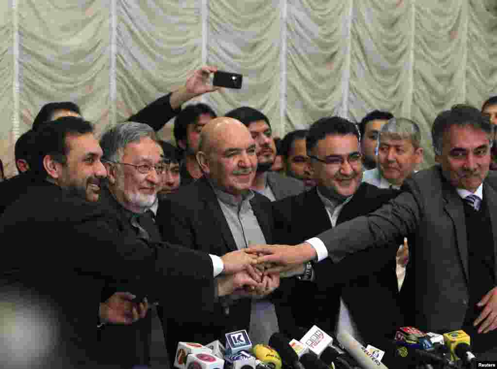 Presidential candidate Zalmai Rassoul (2nd L)  shakes hands with Qayum Karzai (C) and their teams in Kabul, March 6, 2014.  Karzai has announced he is withdrawing from the presidential race.