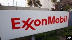FILE - A sign at an ExxonMobil refinery.