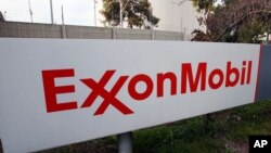 FILE - A sign for the ExxonMobil refinery in Torrance, California, Jan. 30, 2012