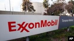 FILE - An ExxonMobil sign sits outside a refinery in Torrance, California.