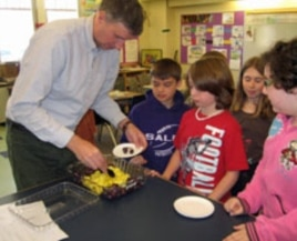 Fourth grade teacher Mark Rampone dishes out the fruit snack for his students.