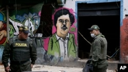 FILE - Police officers stand in front of a mural depicting the late drug kingpin Pablo Escobar, in the area known as El Bronx in downtown Bogota, Colombia, May 30, 2016. The area has been plagued by drug addicts and prostitution, including girls forced into sexual servitude.