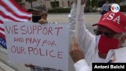 """Dos manifestantes posan junto a un cartel con el mensaje """"Nosotros apoyamos y rezamos por nuestra policía"""" durante una marcha en Miami.[Foto: Antoni Belchi,VOA]"""
