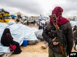 FILE - A member of Kurdish security forces watches as families load their belongings onto trucks before leaving the Kurdish-run al-Hol camp, in the Hasakah governorate in northeastern Syria, Nov. 16, 2020.