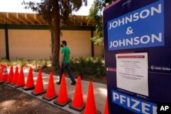 FILE - A man arrives for his appointment to get vaccinated, as banners advertise the availability of the Johnson & Johnson and Pfizer COVID-19 vaccines at a county-run vaccination site at the Eugene A. Obregon Park in Los Angeles, July 22, 2021.