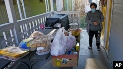 Evelyn Maysonet looks at the food delivery from the Weber-Morgan Health Department Tuesday, Nov. 24, 2020, in Ogden, Utah. Maysonet has been isolating with her husband and son in their Ogden home since all three tested positive for COVID-19 over a week…