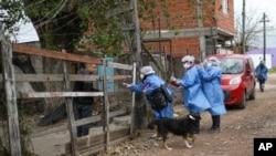 Trabajadores sanitarios entrevistan a un residente fuera de su casa en el barrio de Villa Azul, aislado en cuarentena después de que más de 50 residentes dieron positivo del nuevo coronavirus en las afueras de Buenos Aires, Argentina.