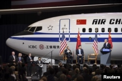Chinese President Xi Jinping (C) and Ray Conner (L), president of Boeing Commercial Airplanes, watch as Boeing Co Chief Executive Dennis Muilenburg (R) stands at a podium, after Xi's tour of the Boeing assembly line in Everett, Washington, Sept. 23, 2015.