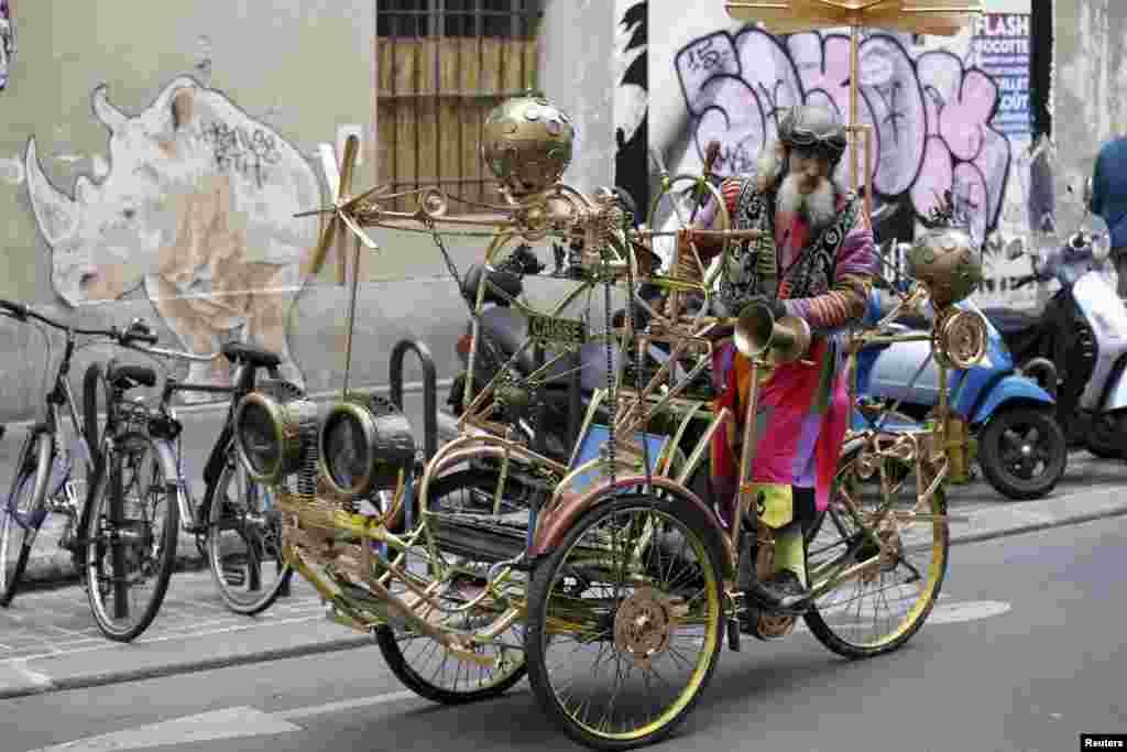 សិល្បករជនជាតិបារាំង លោក Gino ជិះស៊ីក្លូ ដែលមានឈ្មោះថា «Celestial Cyclo» ដែលផលិតដោយលោកផ្ទាល់នៅក្នុងសង្កាត់ Le Marais ក្នុងក្រុងប៉ារីស កាលពីថ្ងៃទី១៥ ខែសីហា ឆ្នាំ២០១៥។