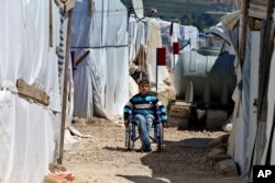 FILE - A disabled Syrian refugee boy sits in his wheelchair in a refugee camp in the town of Bar Elias, in Lebanon's Bekaa Valley, April 23, 2018.