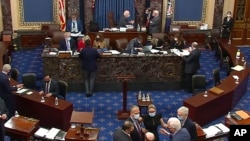 FILE - In this image from video, lawmakers and staff members confer on the floor of the Senate at the U.S. Capitol in Washington, Feb. 13, 2021.