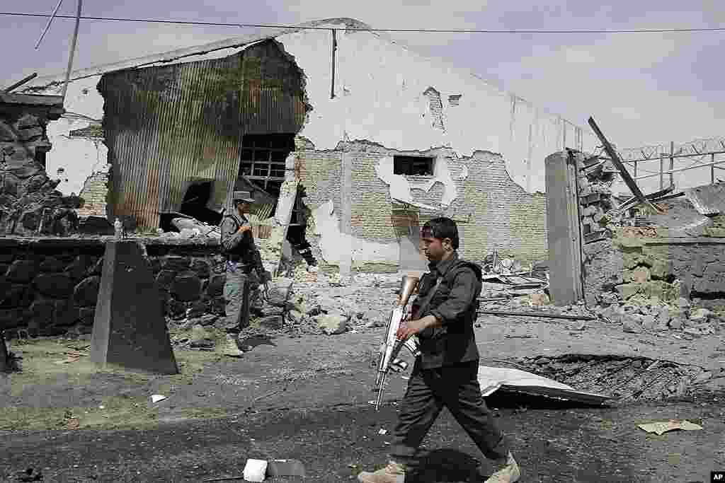 Un policía afgano camina frente al complejo afectado por la explosión causada por el ataque terrorista en Kabul, Afganistán. (AP Photo/Ahmad Jamshid)