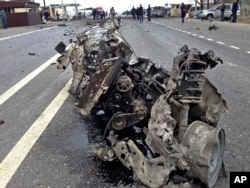FILE - The wreckage of a suicide bomber's car is seen near a traffic police check point near Derbent in Russia's northern Caucasus region of Dagestan, Feb. 15, 2016.