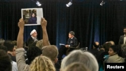FILE - A protester holds up a picture of Ghoncheh Ghavami as Iran's President Hassan Rouhani (L) speaks with moderator Fareed Zakaria at New America, a public policy institute and think tank in New York, Sept. 24, 2014.