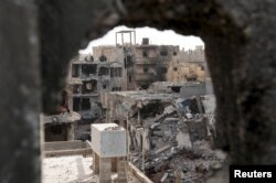 FILE - Damaged buildings are pictured after clashes between members of the Libyan pro-government forces and the Shura Council of Libyan Revolutionaries, an alliance of former anti-Gaddafi rebels who have joined Islamist group Ansar al-Sharia, in Benghazi, Libya,