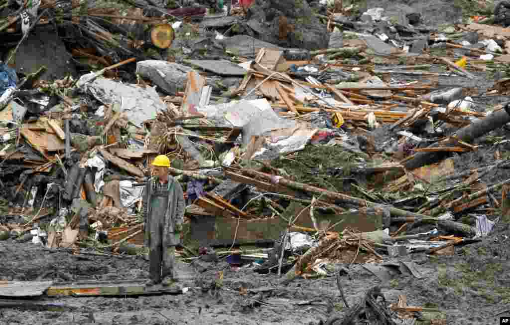 A searcher walks through a massive pile of debris at the scene of a deadly mudslide in Oso, Washington, March 27, 2014.