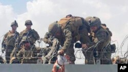 This image from video provided by Omar Haidari and taken, Aug. 19, 2021, shows a baby being lifted across a wall at the Kabul airport in Afghanistan by US soldiers.
