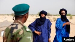 FILE - A Malian soldier speaks with Tuareg men in the village of Tashek, outside Timbuktu, July 27, 2013.