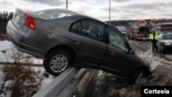 En esta imagen proporcionada por el departamento de Bomberos de Hudson, Nueva Hampshire, se ve a un auto balanceándose en la valla protectora del puente Sagamore.