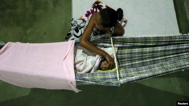 Miriam Araujo, 25, caresses Lucas, her 4-month-old child born with microcephaly as he sleeps on a hammock inside their house, in Sao Jose dos Cordeiros, Brazil, Feb. 16, 2016.