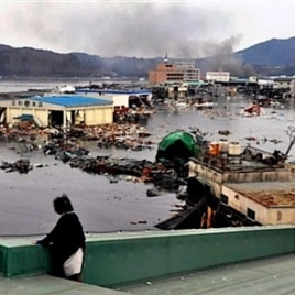 A warehouse and vehicles are washed away in Kesennuma