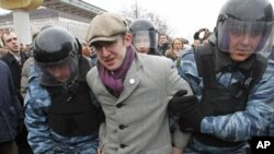 Riot police detain a protester during a rally near the state-controlled TV channel NTV tower in Moscow, March 18, 2012.