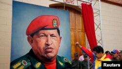 ຮອງປະທານາທິບໍດີ ເວເນຊູເອລາ ທ່ານ Nicolas Maduro ກໍາລັງ ຍົກກໍາປັ້ນໃຫ້ກຽດແກ່ ຮູບແຕ້ມ ປະທານາທິບໍດີ Hugo Chavez