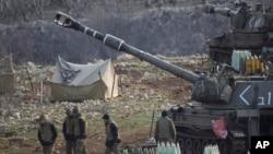 Tentara Israel berdiri dekat unit artileri bergerak di Dataran Tinggi Golan dekat perbatasan dengan Suriah (28/1). (AP/Ariel Schalit)