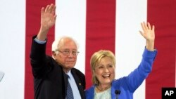 Democratic presidential candidate Hillary Clinton and Sen. Bernie Sanders wave to supporters with during a rally in Portsmouth, N.H., where Sanders endorsed her for president, July 12, 2016.