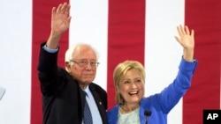 លោក Bernie Sanders និងលោកស្រី Hillary Clinton លើកដៃទៅកាន់អ្នកគាំទ្រនៅក្នុងការឃោសនាបោះឆ្នោតនៅក្រុង Portsmouth ក្នុងរដ្ឋ New Hampshire កាលពីថ្ងៃទី១២ ខែកក្កដា។