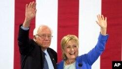 Ứng cử viên tổng thống của đảng Dân chủ Hillary Clinton và Thượng nghị sĩ Bernie Sanders vẫy chào những người ủng hộ trong một cuộc mít tinh ở Portsmouth, New Hampshire, 12/7/2016.