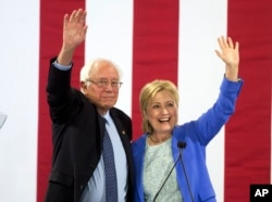 FILE - Hillary Clinton and Sen. Bernie Sanders wave to supporters during a rally in Portsmouth, N.H., where Sanders endorsed her for president, July 12, 2016.