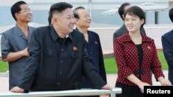 North Korean leader Kim Jong Un and a woman being identified by state TV as his wife 'Comrade Ri Sol Chu,' visit the Rungna People's Pleasure Ground, which is nearing completion, in Pyongyang, July 25, 2012.