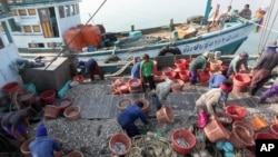 Migrant workers work on fishing boats at a pier in Prachuabkhirikhant province, southern Thailand Tuesday, March 4, 2014.