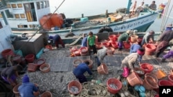 Migrant workers work on fishing boats at a pier in Prachuabkhirikhant province, southern Thailand Tuesday, March 4, 2014. An environmental and human rights group charged Tuesday that Thailand is not adequately addressing severe abuse against migrant workers in the Thai fishing industry. (AP Photo/Apichart Weerawong)