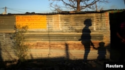 FILE - The shadows of a mother and child are cast on a shack in Marikana's Nkaneng township in Rustenburg, northwest of Johannesburg, South Africa, Aug. 15, 2013.