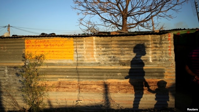 The shadows of a mother and child are cast on a shack in Marikana's Nkaneng township in Rustenburg, 100 km (62 miles) northwest of Johannesburg, August 15, 2013.