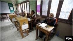 Petugas pemilu Mesir menunggu datangnya para pemilih dalam pemilu parlemen babak kedua di sebuah TPS di Kairo (6/12).