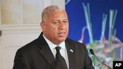 """FILE - Fiji Prime Minister Frank Bainimarama, pictured speaking in Suva, Sept. 6, 2013, says """"cities in the developed world like Miami, New York, Venice or Rotterdam"""" are as vulnerable to rising seas as tropical islands."""