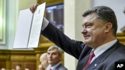Presiden Ukraina Petro Poroshenko menunjukkan persetujuan Ukraina-Uni Eropa kepada parlemen (16/9) di Kyiv. (AP/Mykola Lazarenko)