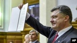 El presidente ucraniano Petro Poroshenko muestra el acuerdo de acercamiento con la Unión Europea.
