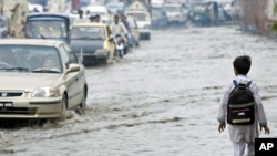 A boy walks near vehicles through a flooded street after heavy rains in Peshawar August 25, 2011
