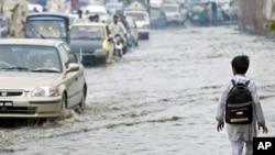 A boy walks near vehicles through a flooded street after heavy rains in Peshawar August 25, 2011