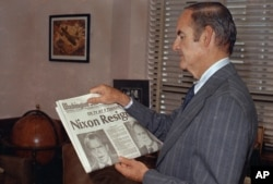 Sen. George McGovern (D-SD) reads the newspaper headline of President Nixon's resignation, Aug. 7, 1974.