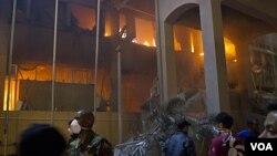 Pasukan pro-Gaddafi dan warga Tripoli mengamati bangunan yang baru dihantam serangan udara NATO (17/5).