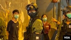 兩名高舉抗議警方標語的年輕人被警員截查。(美國之音湯惠芸)